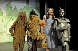 The cowardly lion, the scarecrow, toto, Dorothy and the tin man on the road to Oz