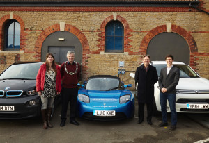 Frome's Town Mayor Peter Macfadyen (wearing his solar powered Mayors Chain) with Zero Carbon World Trustees; Cara Naden, Kevin Sharpe and Alexander Sims, with a selection of Electric Cars charging at the Cheese & Grain's Zero Carbon World Charging Stations and the building's Solar Panels - Photo: Joe Hulbert