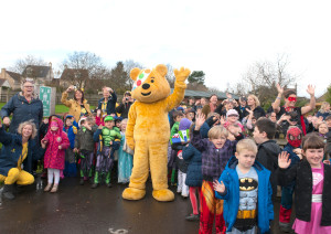 Staff, pupils and Pudsey Bear wave with excitement as the helicopter makes a special flyby at Christ Church First School.