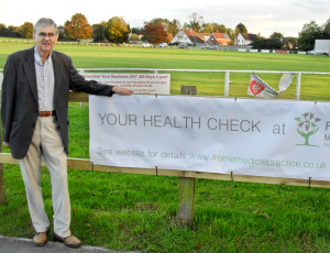 Paul Lewis, vice-chair of the Patient  Participation Group with the health  check banner outside the health centre.